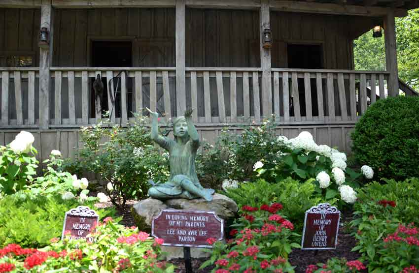 Dolly Parton rose in front of reproduction cabin